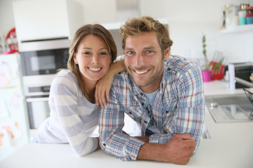 Portrait of couple standing in modern kitchen